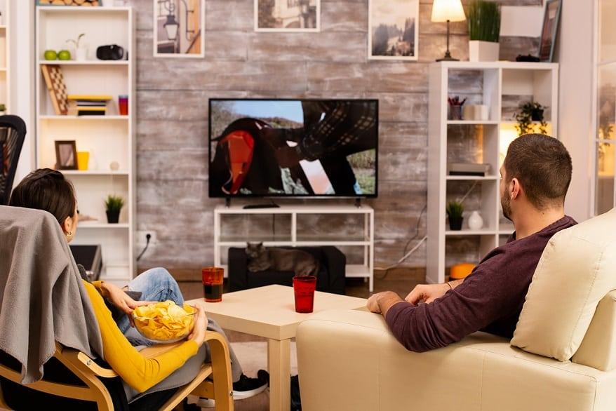 זוג יושב בסלון וצופה בסדרה שהוא אוהב על מחנאות