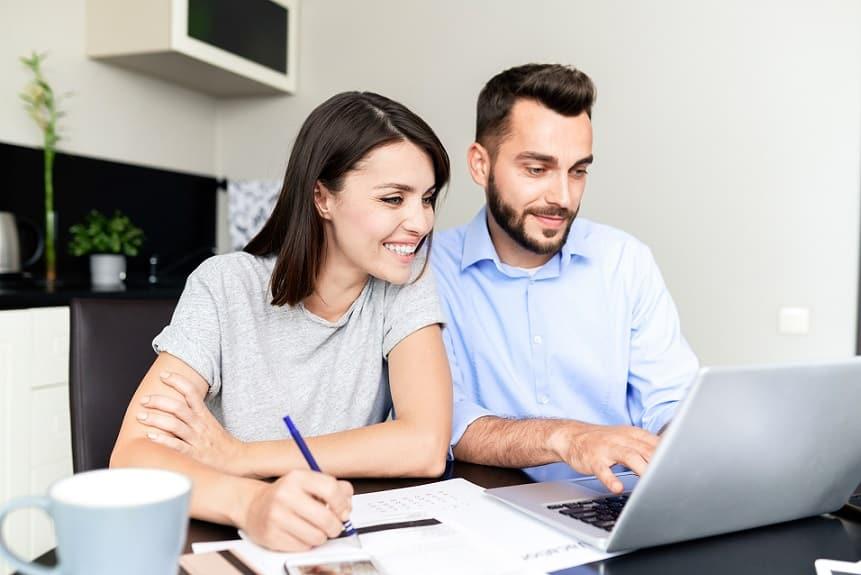 זוג צעיר קורא מדריכים שונים באינטרנט ורושם הערות