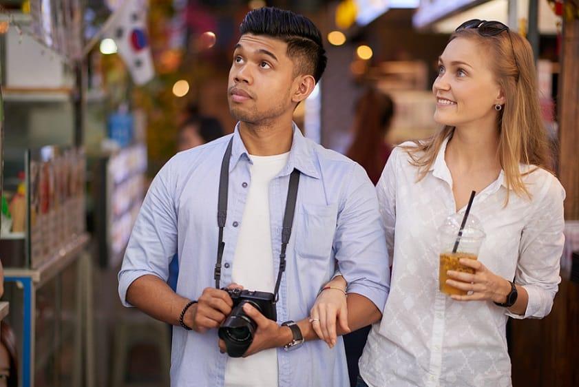 זוג תיירים מחזיקים ידיים ומחפשים דברים לצלם בחופשה שלהם