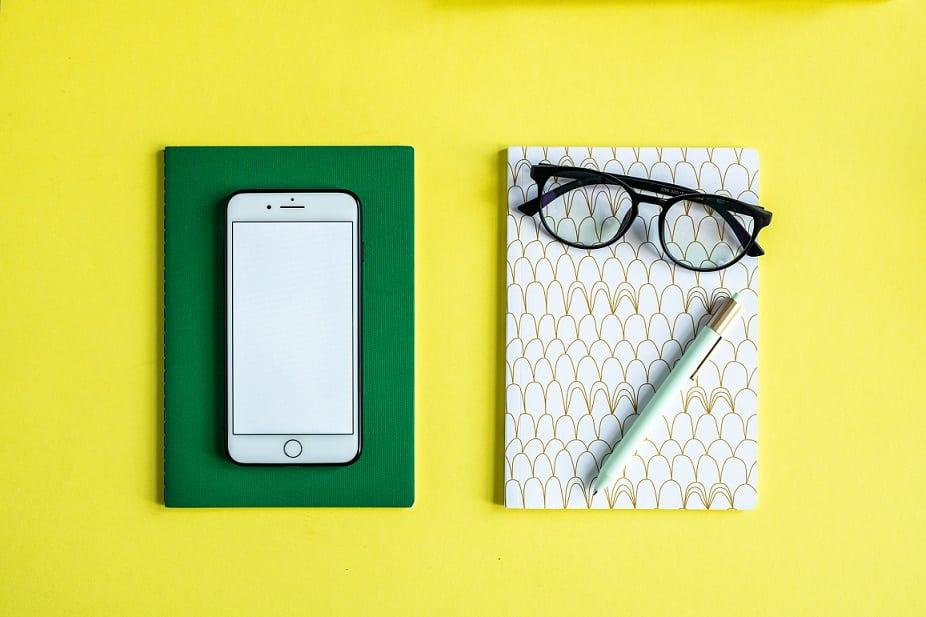 טלפון סלולרי מונח על מחברת ירוקה על רקע צהוב