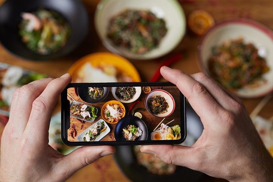 ידיים מחזיקות טלפון נייד ומצלמות את השולחן מלא האוכל