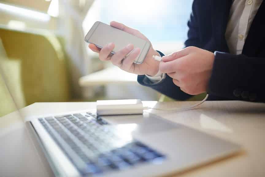 ידיים מנסות לחבר את המטען אל הפלאפון כדי להטעין את הסוללה