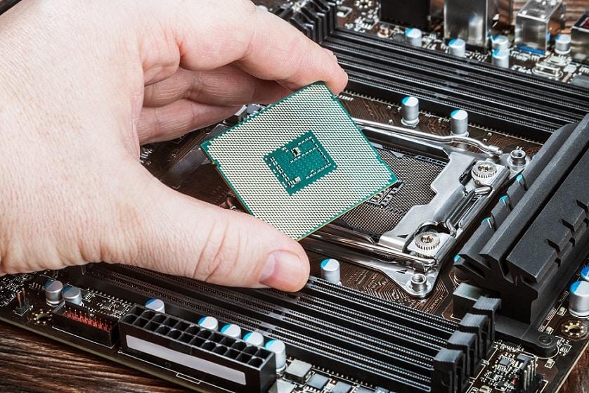 יד מחזיקה מעבד של מחשב ומכניסה אותו לאיזור המתאים