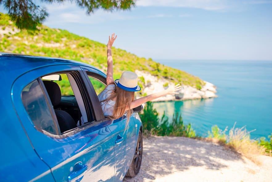 ילדה קטנה מוציאה את הראש של מתוך מכונית כחולה בזמן חופשה