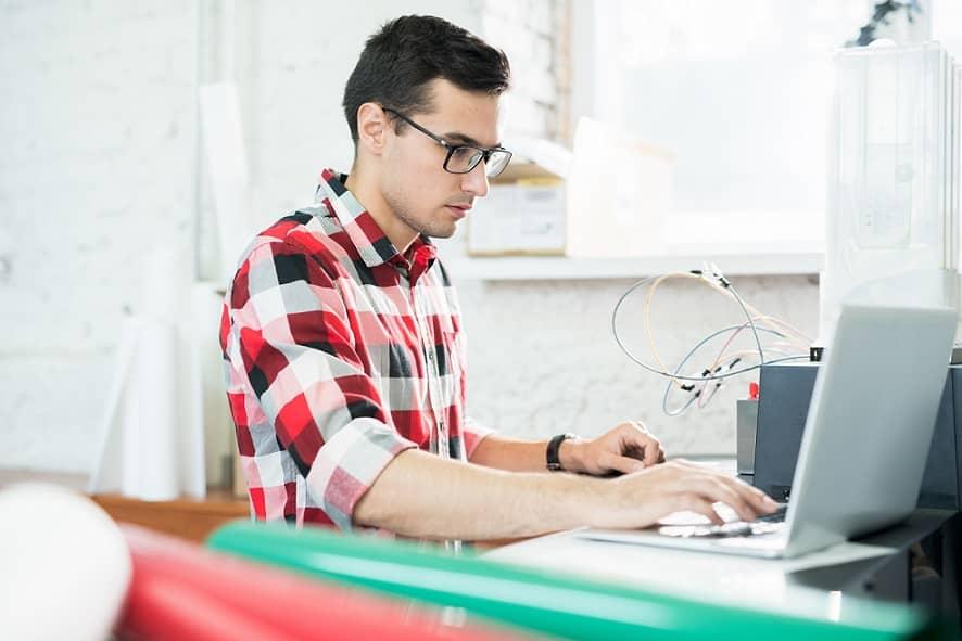 מהנדס צעיר בודק מוצרים שונים על המחשב שלו ועושה השוואה