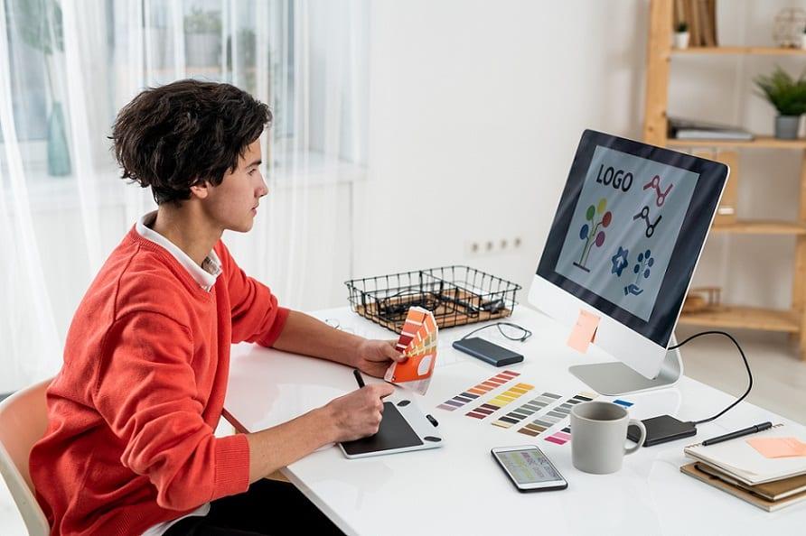 מעצב צעיר עובד על עיצוב של לוגואים על המחשב שלו