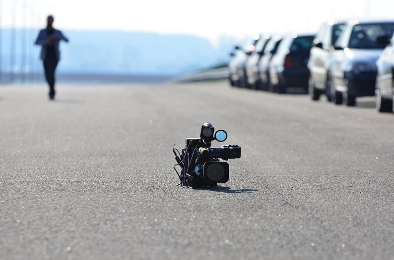 מצלמה גדולה שנועדה לצלם סרטונים מונחת על הכביש עם בן אדם ברקע