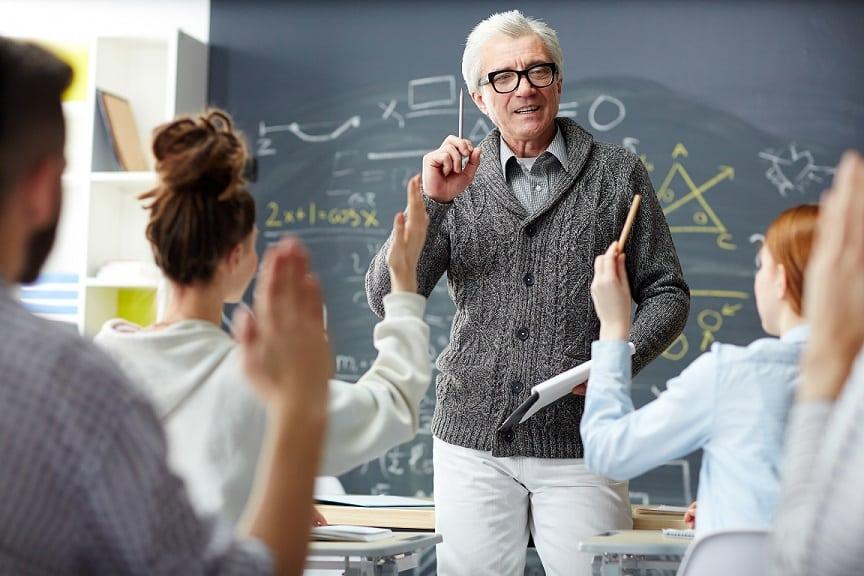 מרצה מבוגר עם שיער לבן עונה על שאלות של סטודנטים בכיתה