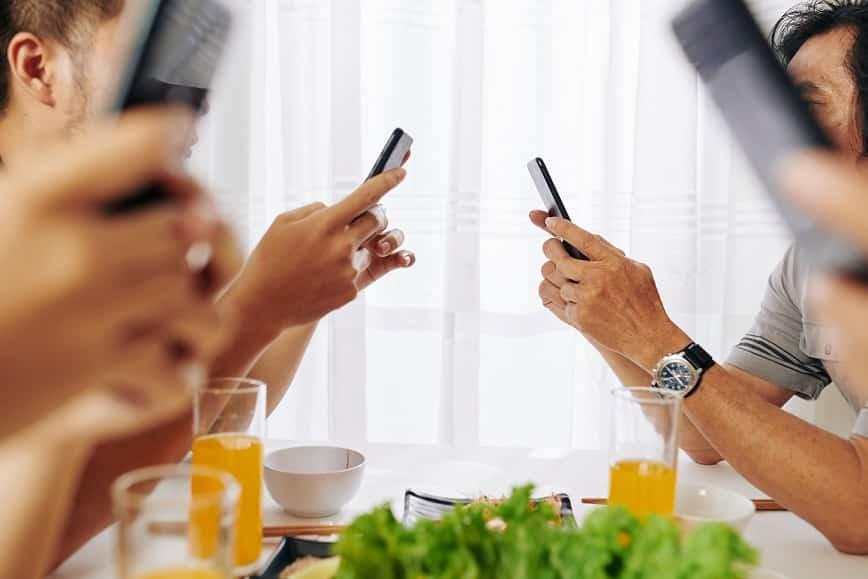 משפחה יושבת בשולחן האוכל וכל אחד מסתכל במסך של המכשיר שלו