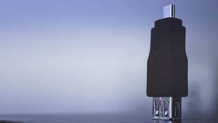 מתאם USB שחור עומד על רקע כחול עם אור לבן