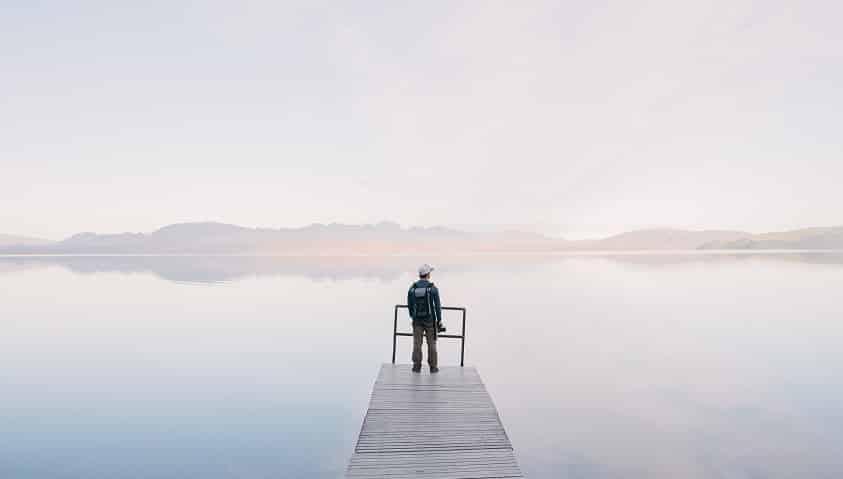צלם עומד מול הים לובש כובע ועל הגב יש לו תיק והוא מסתכל אל האופק