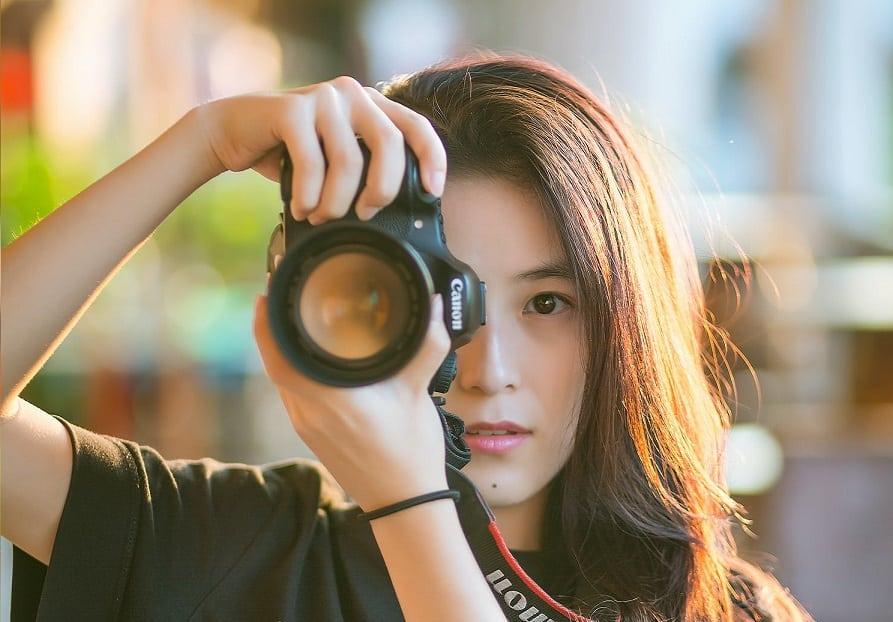 צלמת צעירה ממוצא אסייתי מצלמת את המסך ומסתכלת עליו עם העין השנייה