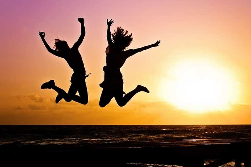 2 אנשים קופצים משמחה באוויר על החוף כשברקע השמש שוקעת