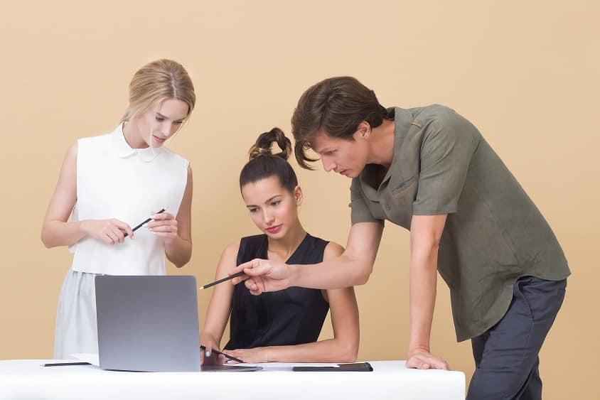 3 אנשים מסתכלים על המסך של המחשב ומנהלים דיון מקצועי
