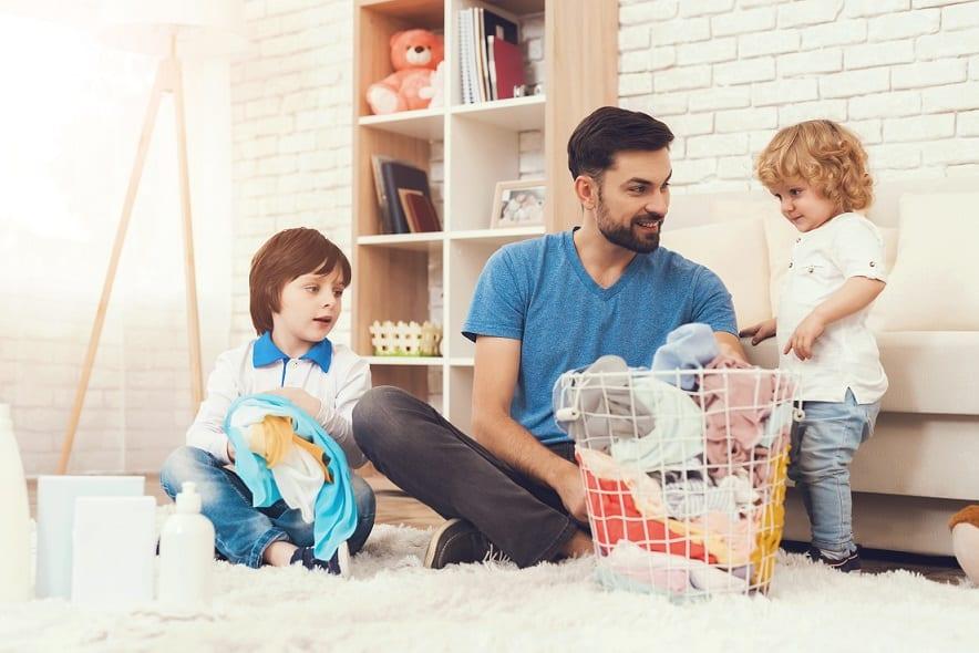 אבא מראה לילדים שלו איך להתעסק עם כביסה