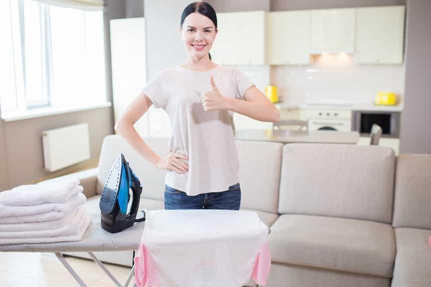 אישה ליד מכשירים לטיפול בבגדים עושה סימן של הכל בסדר