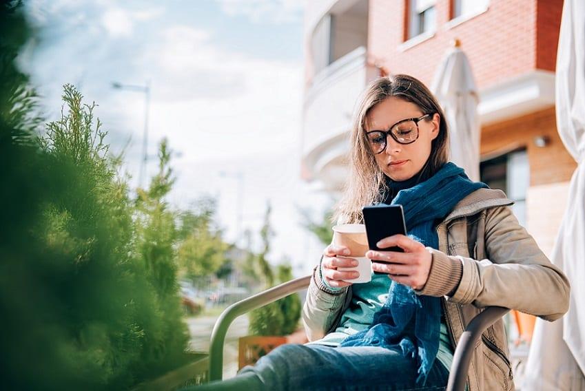 אישה עם משקפיים קוראת מדריכים בפלאפון שלה בחוץ