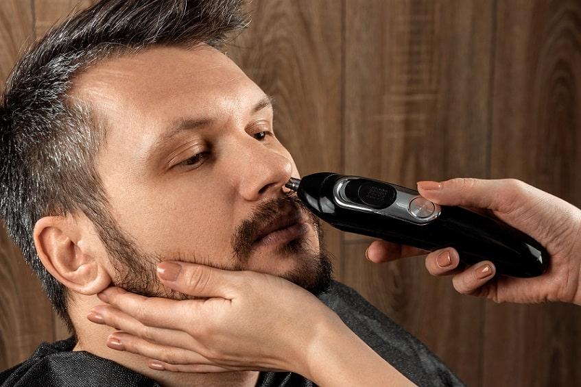 איש מקצוע עושה קיצוץ שיער באף ללקוח שלו