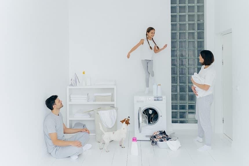 אמא אבא והילדה שלהם עושים כיף בחדר הכביסה הלבן