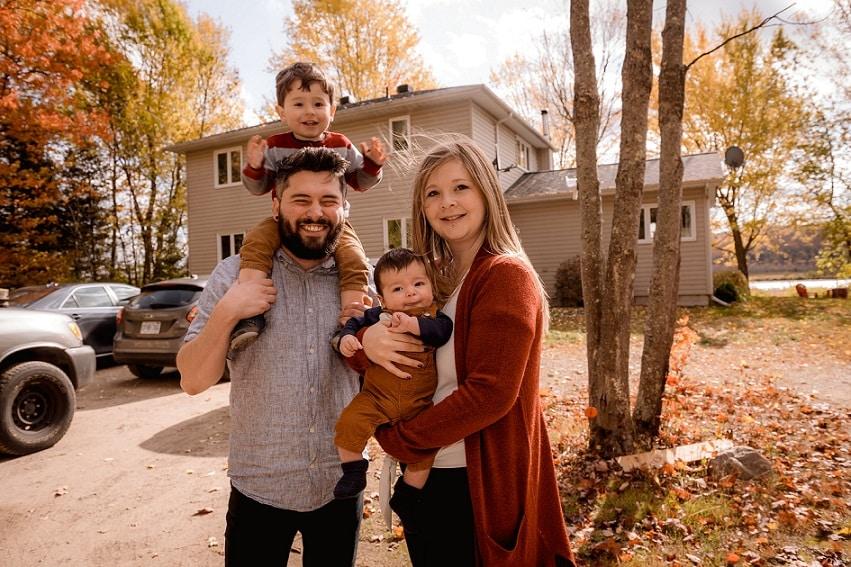 אמא אבא ו-2 ילדים קטנים עומדים בחצר של הבית על רקע האביב