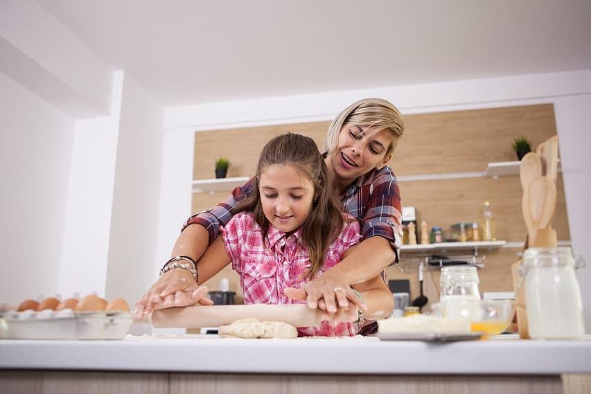 אמא מלמדת את הבת שלה איך ללוש בצק עם מערוך