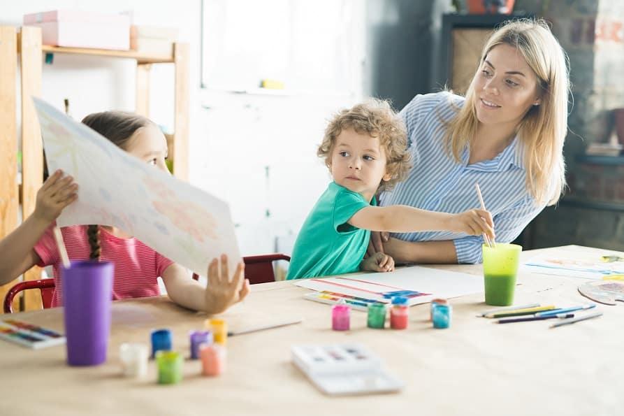 אמא עוזרת לילדים שלה להכין שיעורי בית באומנות בסדנה הביתית