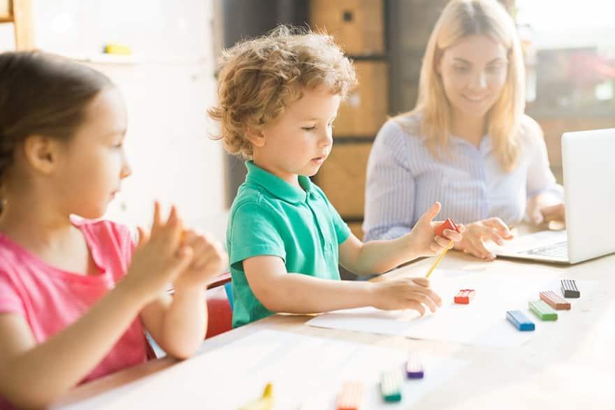 אמא קוראת מדריכים על צעצועים שונים בזמן שהילדים שלה יושבים ויוצרים