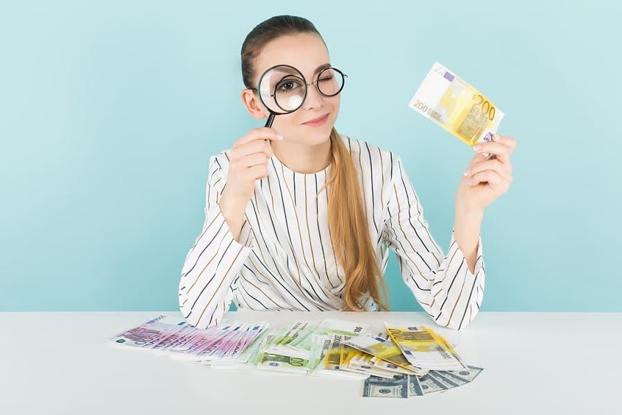 בחורה בודקת שטרות של כסף תחת זכוכית מגדלת