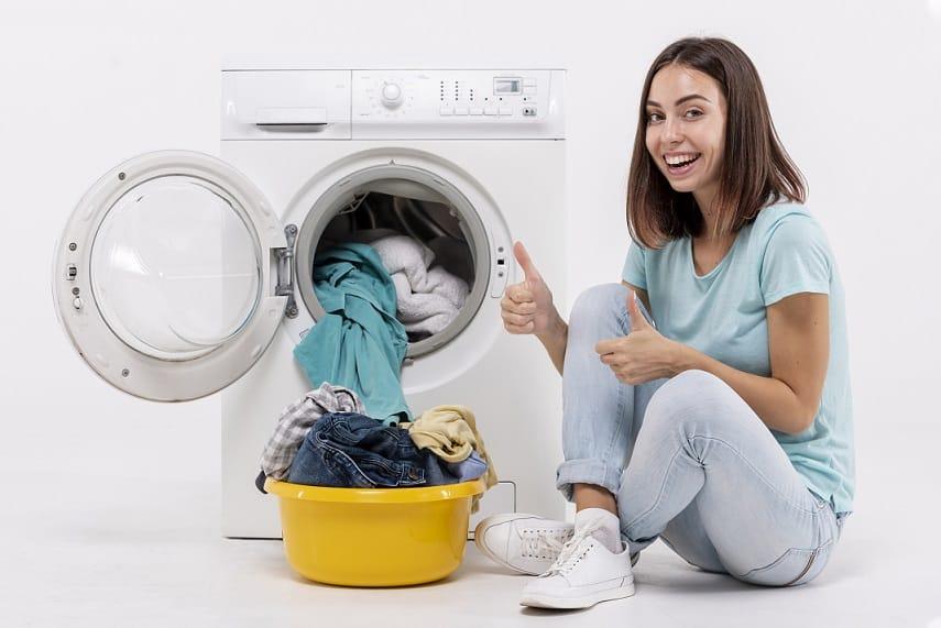 בחורה יושבת על הרצפה ליד מכונת כביסה ועושה סימן של הכל מעולה