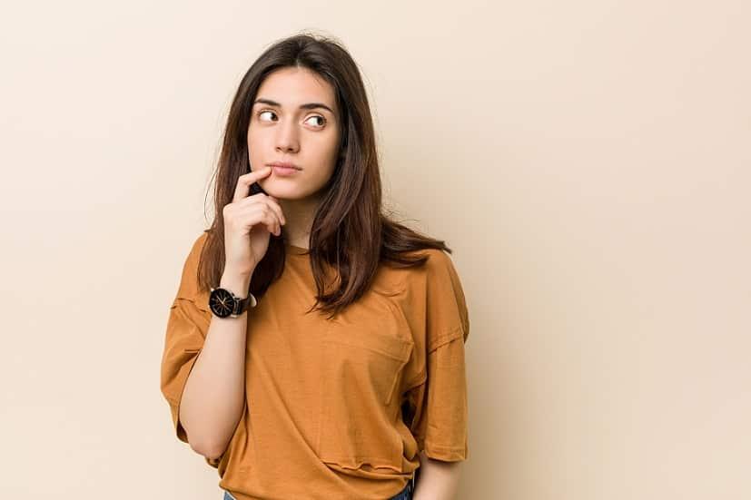 בחורה עם חולצה כתומה חושבת על שאלות שונות ומסתכלת למעלה