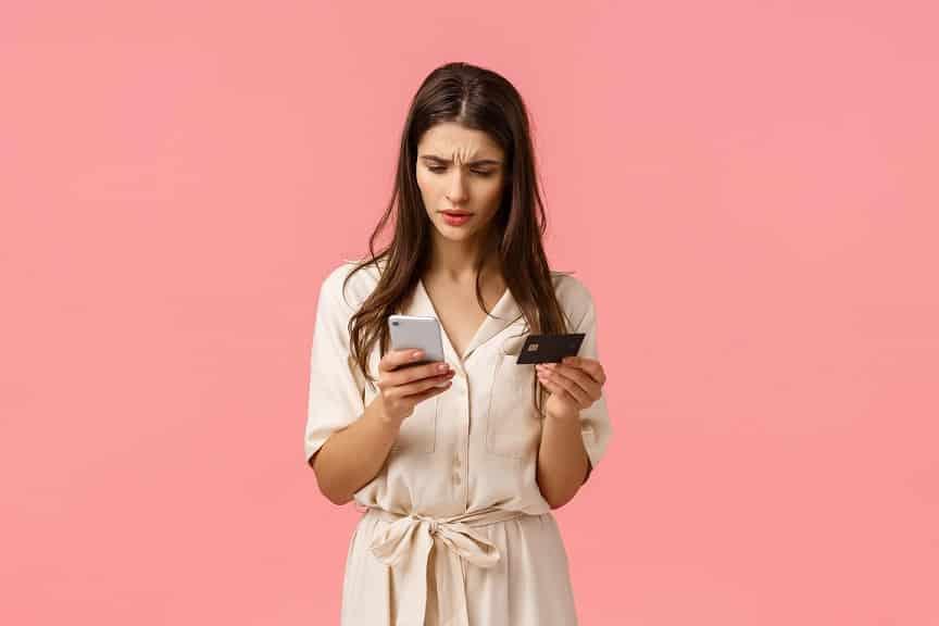 בחורה עם שיער ארוך מחזיקה אשראי ומשווה מחירים בטלפון