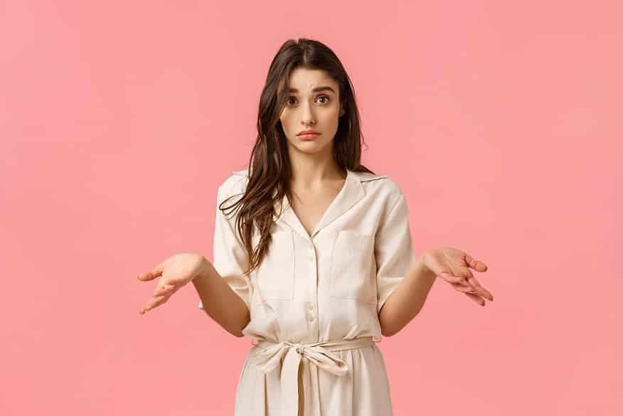 בחורה עם שיער ארוך עושה תנועה של שאלה עם הידיים רקע ורוד
