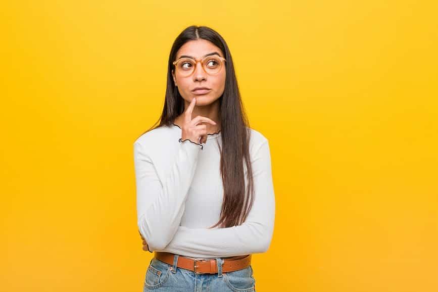 בחורה עם שיער ארוך על רקע צהוב חושבת על שאלות