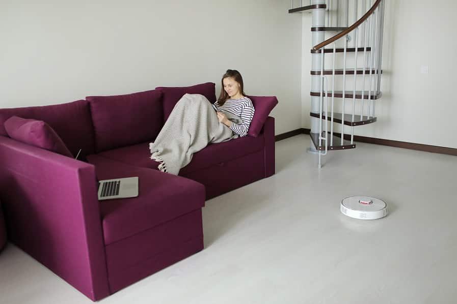 בחורה קוראת על ספה סגולה בזמן שהרובוט מנקה את הבית