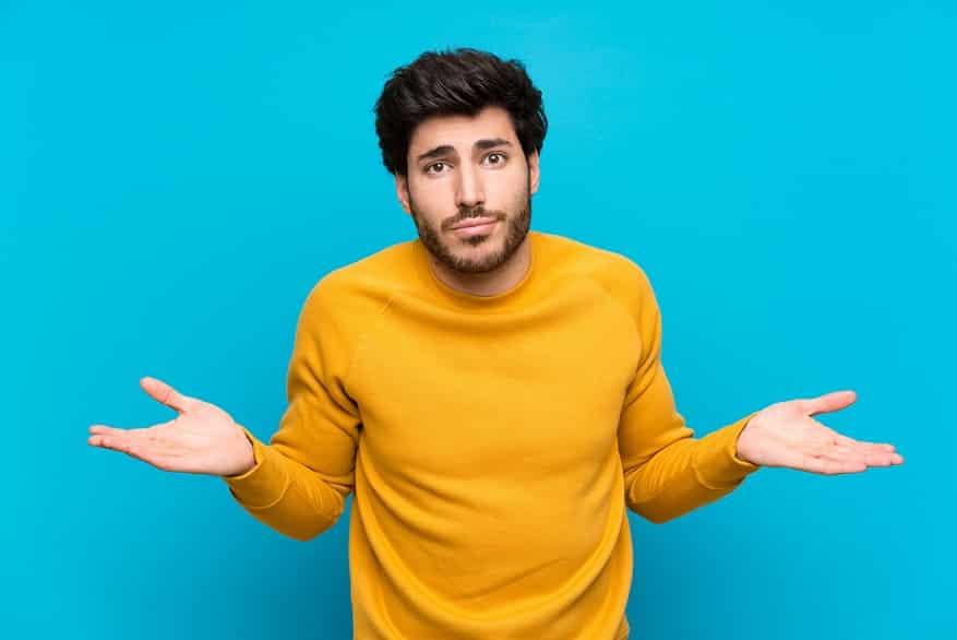 בחור צעיר עם חולצה צהובה עושה תנועה של שאלה עם הידיים