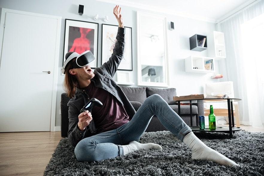 בחור שמח משחק עם משקפיים מיוחדות על הרצפה בסלון