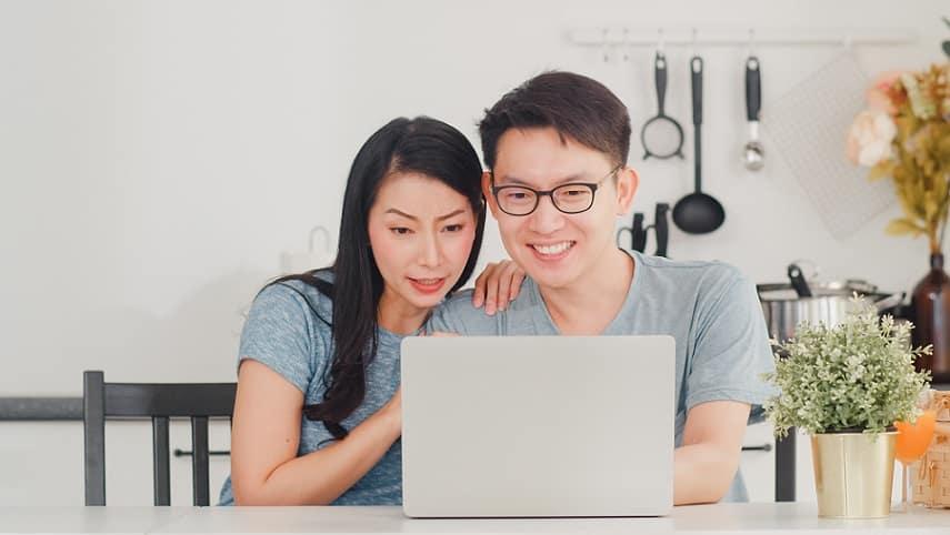 בעל ואישה אסייתים קוראים מדריכים באינטרנט ומחייכים