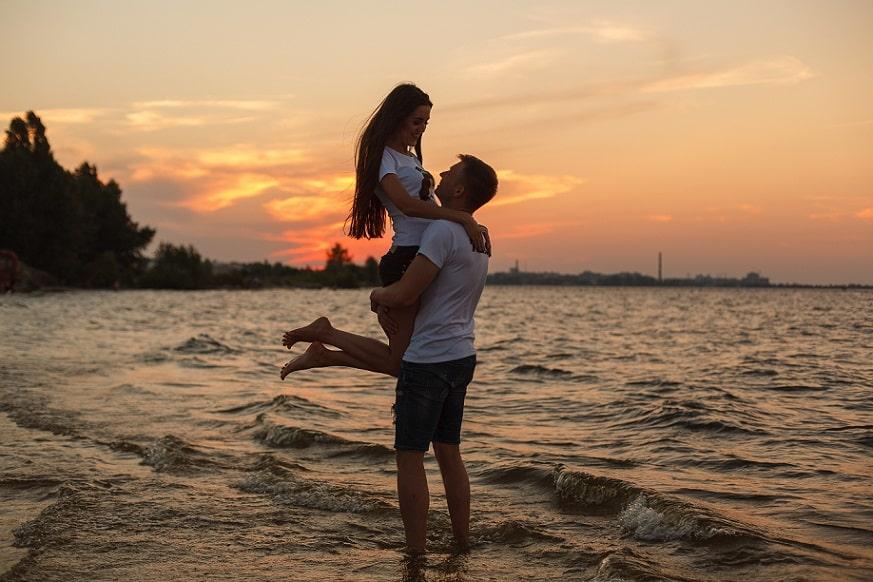גבר מרים את חברה שלו בחוף הים על רקע השקיעה