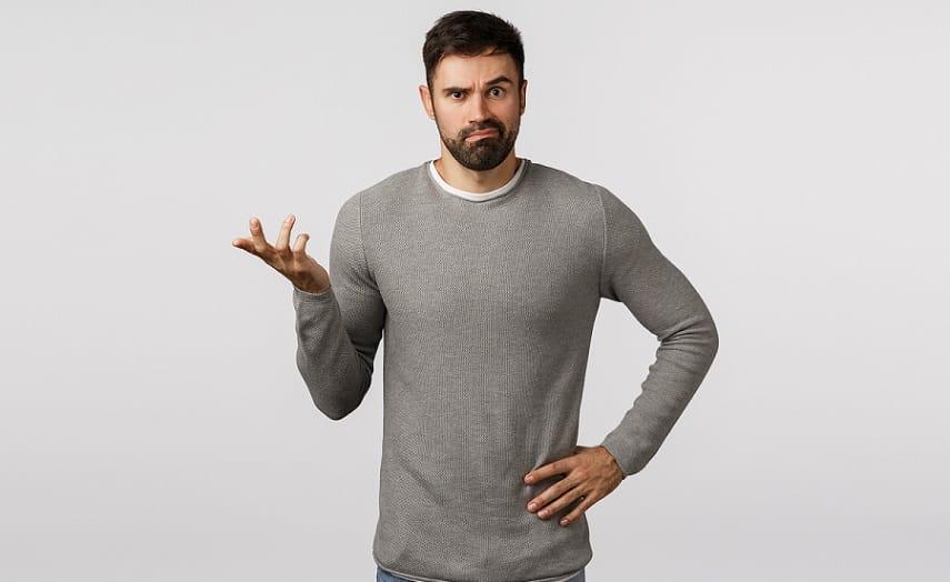 גבר עם שיער קצר וחולצה אפורה עושה תנועה של שאלה