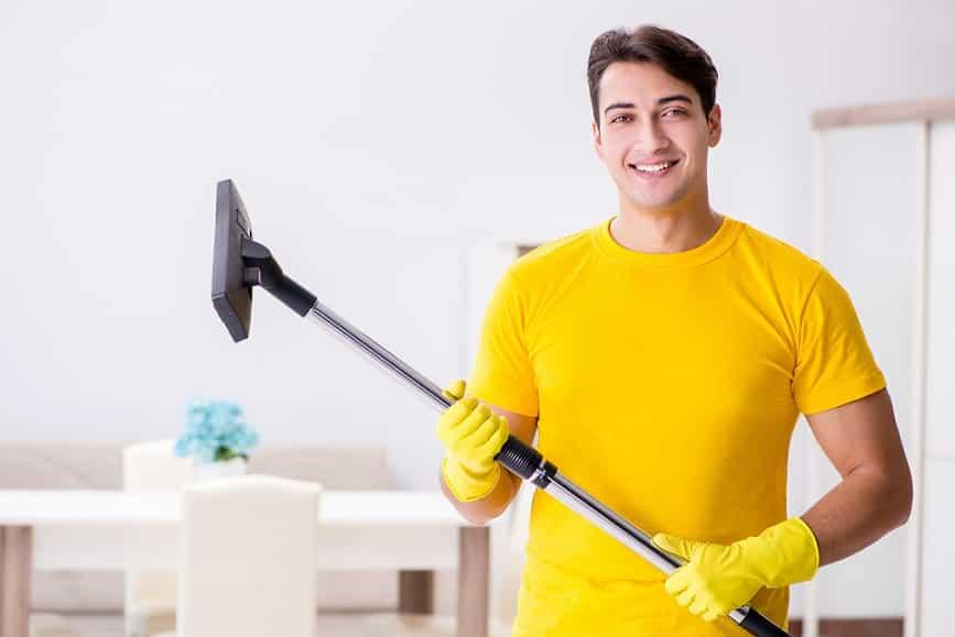 גבר צעיר עם חולצה צהובה מחזיק מוט של שואב אבק ומחייך