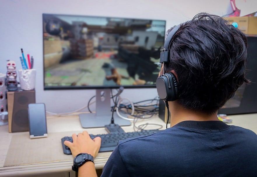 גיימר משחק במשחק על המחשב שלו עם אוזניות