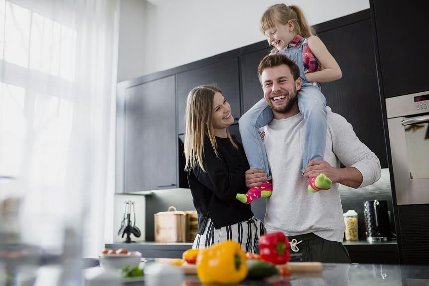 הורים משחקים עם הילדה שלהם במטבח ומחייכים