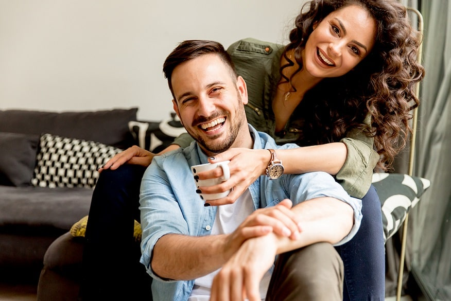 זוג מאושר מתחבק ומביט למצלמה עם חיוך