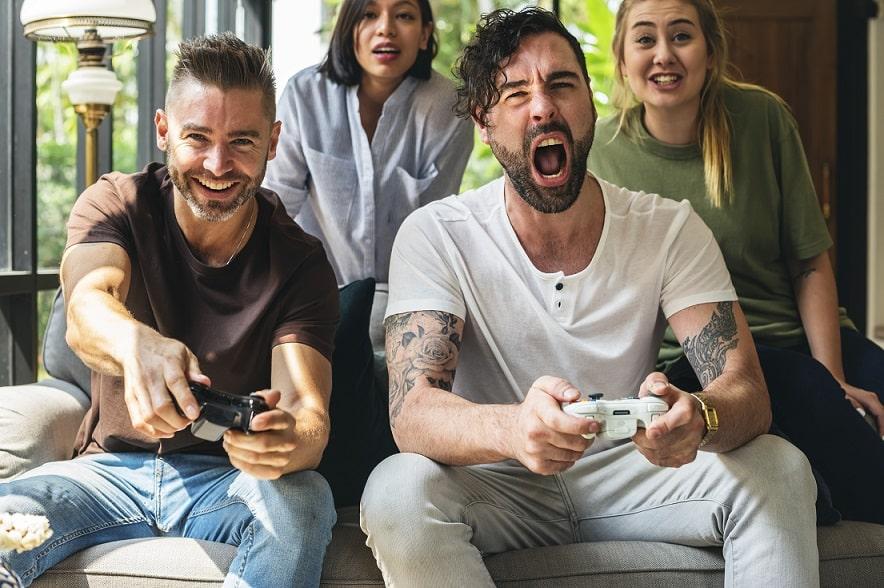 חברים ובנות הזוג שלהם משחקים במשחקי טלוויזיה ביחד וצוחקים