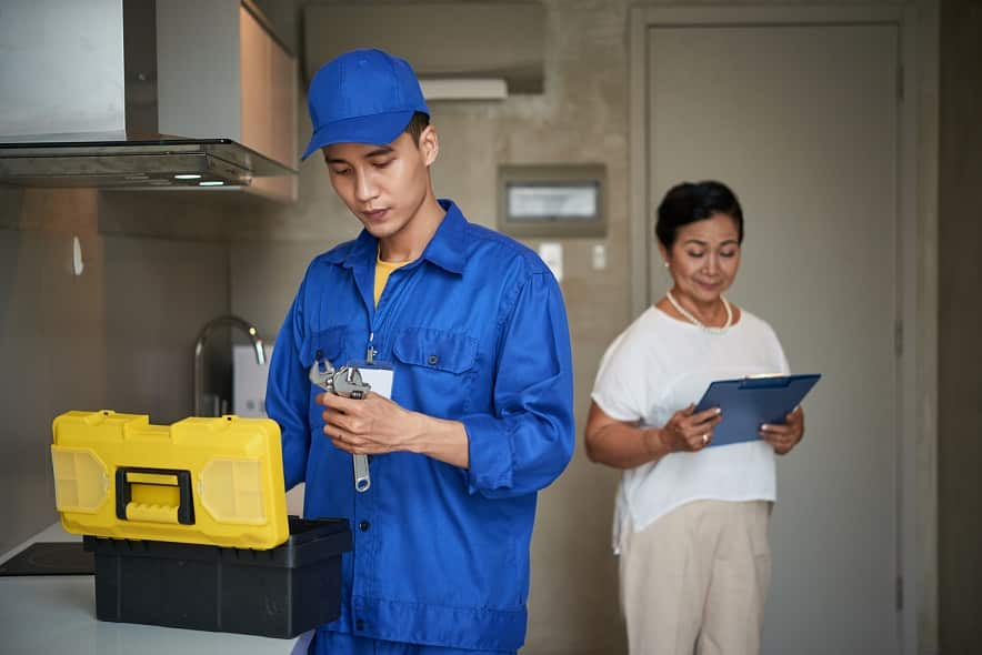 טכנאי במדים כחולים בוחר את כלי העבודה שלו בבית של לקוחה