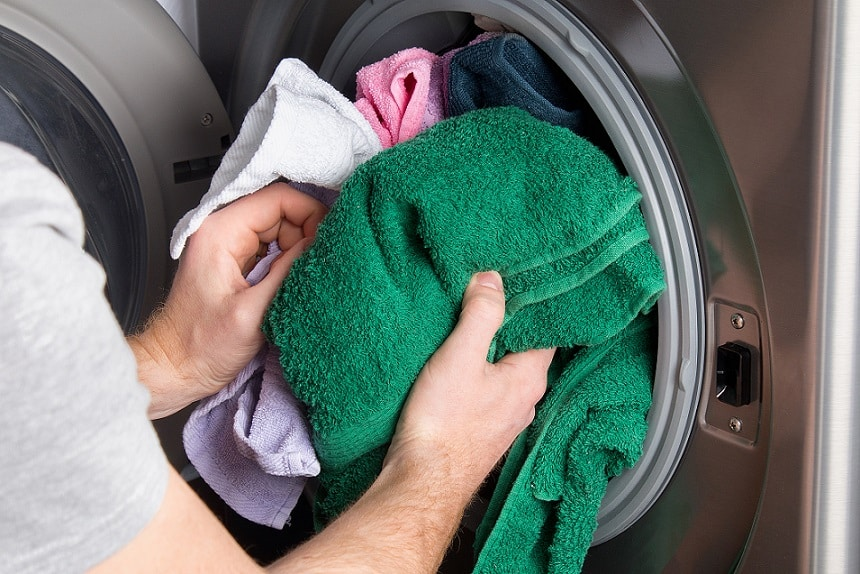 ידיים מכניסות כביסה מלוכלכת למכונת השטיפה