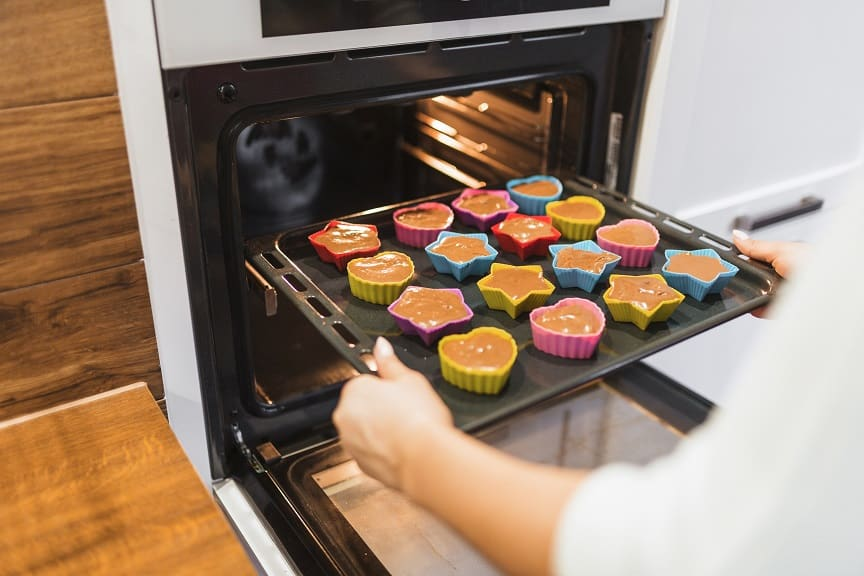 ידיים מכניסות מאפינס לתור תנור אפייה