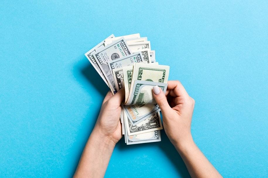 ידיים על רקע כחול סופרות שטרות של כסף דולרים