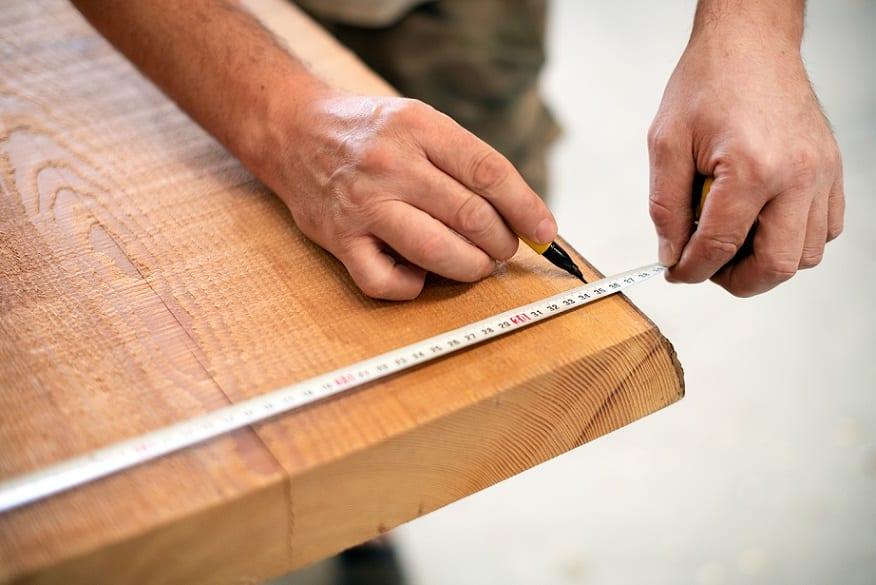 ידיים של גבר מודדות משטח מעץ באמצעות סרט מדידה
