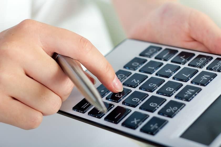 יד לוחצת על כפתורים שונים על גבי מחשבון שחור